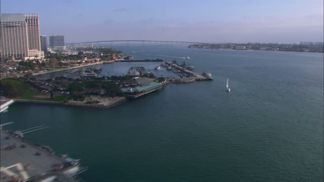AERIAL OF  BOATS IN MARINA. USS MIDWAY, AIRCRAFT CARRIER AND NAVY SHIP. DOCKS. CITY SKYLINE IN BG.