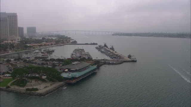 AERIAL OF BOATS IN MARINA, DOCKS. HIGH RISE OFFICE OR APARTMENT BUILDINGS IN CITY SKYLINES. CLOUDY AND OVERCAST.