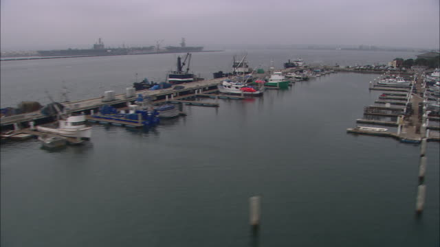 AERIAL OF BOATS IN MARINA, DOCKS. CLOUDY AND OVERCAST.
