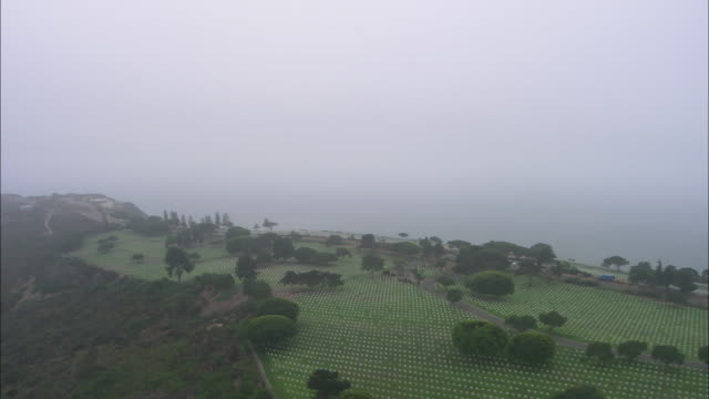AERIAL OF CEMETERY OR GRAVEYARD ON HILL OVERLOOKING PACIFIC OCEAN. CLOUDY AND OVERCAST. FORT ROSECRANS NATIONAL CEMETERY, POINT LOMA.