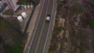 AERIAL OF POLICE CARS FOLLOWING, CHASING PICKUP TRUCK TOWING A BOAT ON TWO-LANE ROAD CEMETERY OR GRAVEYARD. FORT ROSECRANS NATIONAL CEMETERY, POINT LOMA.