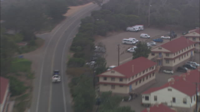 AERIAL OF POLICE CARS FOLLOWING, CHASING PICKUP TRUCK TOWING A BOAT ON TWO-LANE ROAD. POINT LOMA NAVY BASE, MILITARY.