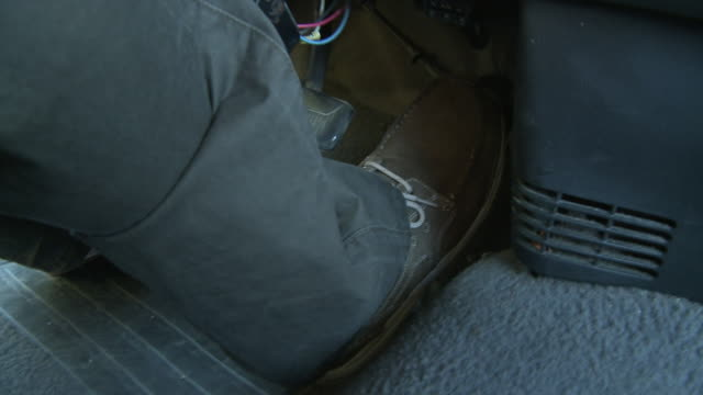CLOSE ANGLE OF HIGH-HEELED SHOE STEPPING ON GAS PEDAL WHILE DRIVING CAR. SERIES.