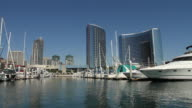 WIDE ANGLE MOVING POV OF BOATS IN MARINA. HIGH RISE OFFICE OR HOTEL BUILDINGS IN BG.