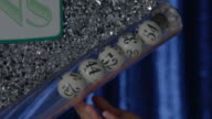CLOSE ANGLE OF LOTTERY BALLS IN MACHINE. HAND VISIBLE.