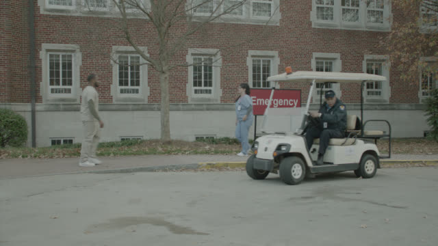 MEDIUM ANGLE OF SECURITY GUARD AT HOSPITAL DRIVING IN GOLF CART.