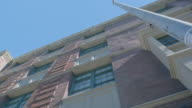 UP ANGLE OF MULTI-STORY BRICK APARTMENT BUILDING.WINDOWS.