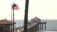WIDE ANGLE OF MANHATTAN BEACH PIER. OCEAN. AMERICAN FLAG.