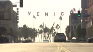 ZOOM IN ON SIGN OVER CITY STREETS AT VENICE BEACH.