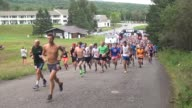 HUNDREDS OF RUNNERS START UP MOUNTAIN ROAD IN RACE HEAD TO CAMERA