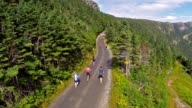 HUNDREDS OF RUNNERS START UP MOUNTAIN ROAD IN RACE AERIAL
