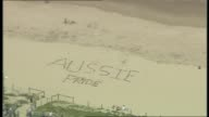 AERIALS CRONULLA MALL AND STREET LARGE CROWDS GATHERED CROWDS SURROUNDING CARS PARKED IN STREET MAN WALKS IN CROWD HOLDING AUSTRALIAN FLAG ALOFT /...