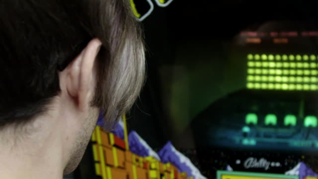 Over the shoulder man playing retro arcade game