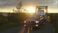 MEDIUM ANGLE OF PICKUP TRUCK TOWING BOAT DRIVING ACROSS TRUSS BRIDGE, FOLLOWED BY SUV OR CAR.