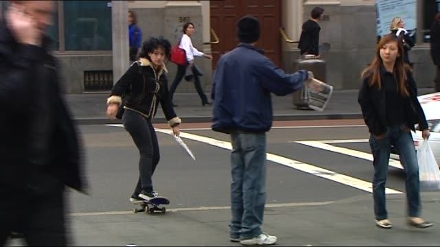 TWO YOUNG PEOPLE MAN AND WOMAN WAITING AT KERB HOLDING SKATEBOARDS AT FEET SEEN FROM ACROSS ROAD AS HEAVY CITY TRAFFIC PASSES IN FRONT OF / WOMAN...
