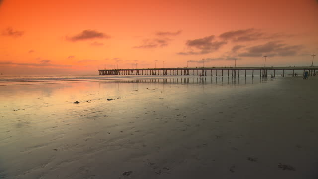 WIDE ANGLE OF SUN SETTING OVER PACIFIC OCEAN. PIER AND BEACH.