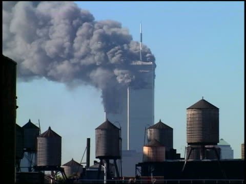 September 11 2001 wide shot World Trade Center Towers burning / water towers in foreground / NYC
