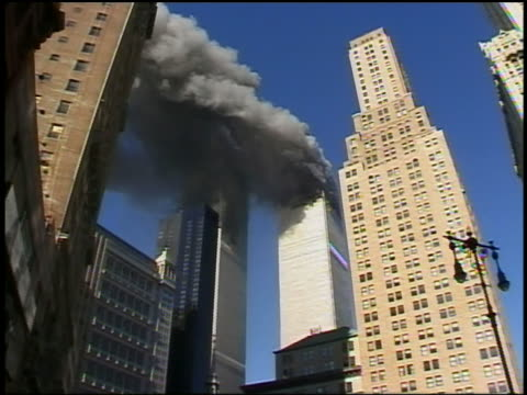 September 11 2001 low angle medium shot smoke pouring out of World Trade Center Tower / other buildings foreground / NYC