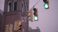 UP ANGLE OF TRAFFIC LIGHTS OR STOP LIGHTS. CHURCH BELL TOWER IN BG.