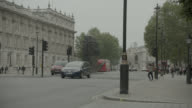 PAN RIGHT TO LEFT OF DOUBLE DECKER BUS DRIVING ON CITY STREET NEAR ENTRANCE TO 10 DOWNING STREET AND GOVERNMENT BUILDINGS. WHITEHALL SW1. PEDESTRIANS, TOURISTS, AND CARS VISIBLE. WOMEN OF WORLD WAR II MONUMNET OR MEMORIAL VISIBLE.