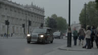 PAN RIGHT TO LEFT OF TAXI DRIVING CITY STREET NEAR ENTRANCE TO 10 DOWNING STREET AND GOVERNMENT BUILDINGS. WHITEHALL SW1. PEDESTRIANS AND TOURISTS VISIBLE. WOMEN OF WORLD WAR II MONUMNET OR MEMORIAL VISIBLE.