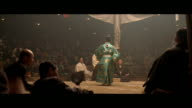 MEDIUM ANGLE OF A SUMO MATCH IN AN ARENA OR AUDITORIUM. TWO WRESTLERS SQUARE OFF AS A REFEREE IN A FANCY GREEN AND YELLOW ROBE WATCHES CLOSELY. REFEREE WEARS A BLACK HAT. MATCH ENDS AND CROWD APPLAUDS. WRESTLERS BOW AND LEAVE RING AND A MAN WITH A WHITE F