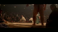 MEDIUM ANGLE OF A SUMO WRESTLING MATCH IN AN ARENA OR AUDITORIUM. CROWD APPLAUDS AS TWO WRESTLERS FACE OFF. REFEREE IN FANCY GREEN AND YELLOW ROBE WATCHES MATCH. ONE WRESTLER IS THROWN FROM RING AND LANDS ON A PHOTOGRAPHER. HE REENTERS RING, WRESTLERS BOW