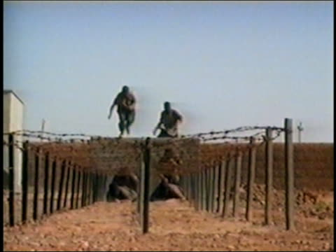 Al Qaeda members training by jumping down from wall / crawling under barbed wire / AUDIO
