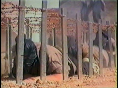 Shaky CU masked Al Qaeda members crawling in cages under barbed wire / AUDIO