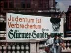 1938 medium shot AntiSemitic billboard sign w/caricature of Jewish man / Austria