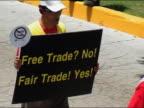 2003 medium shot tracking shot man carrying 'Free Trade No Fair Trade Yes' poster at WTO protest / Cancun Mexico