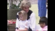CROWD LINED DOWN STREET / PRINCESS DIANA WITH KIDS AT BARNARDO CENTRE / CHILD ON DIANA'S LAP / KIDS IN PLAY GROUND / DIANA HOLDING AND HUG FOR YOUNG...
