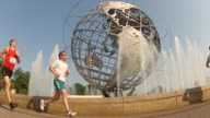 UNISPHERE WITH FOUNTAINS GOING RUNNERS GO BY
