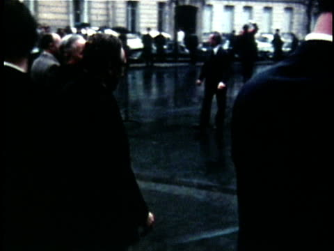 Henry Kissinger and Vietnamese official Le Duc Tho shaking hands on street after peace talks / Paris France