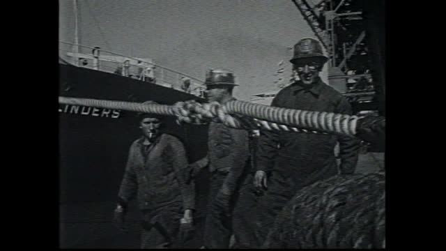 CARGO TANKER SHIP IRON FLINDERS SAILS SMOKE BILLOWS FROM STACK WIDE SHOT WITH TUG BOAT PILOT CLOSE UP OF NAME ON HULL DOCK WATERSIDE WORKERS RUN ROPE...