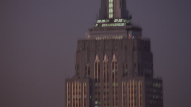 AERIAL OF TOP OF EMPIRE STATE BUILDING, ZOOMS IN, THEN PANS DOWN AND UP.