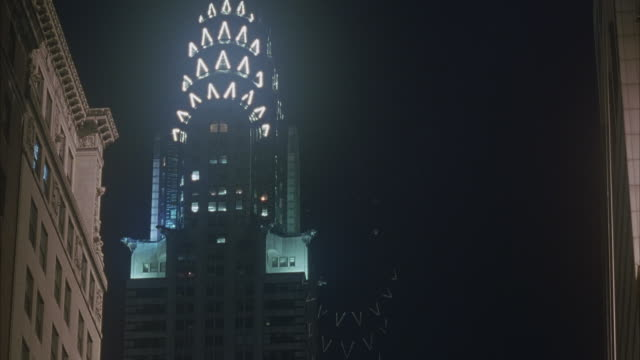 MEDIUM ANGLE OF CHRYSLER BUILDING AT NIGHT. LIT UP. SEE TIP OF BUILDING CUT OFF IN SHOT.