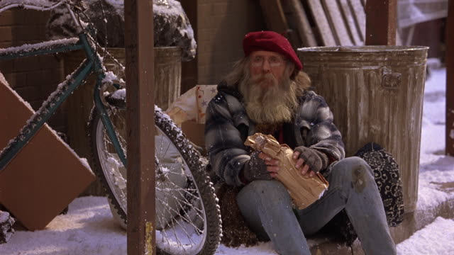 MEDIUM ANGLE OF A HOMELESS MAN IN A RED BERET SITTING ON SNOW COVERED GROUND HOLDING A LARGE BOTTLE WRAPPED IN A BROWN PAPER BAG.  LOOKS LIKE AN OLD HIPPIE. A SNOW COVERED BIKE NEXT TO HIM.