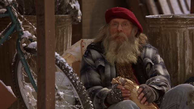 CLOSE ANGLE OF A HOMELESS MAN IN A RED BERET SITTING ON SNOW COVERED GROUND HOLDING A LARGE BOTTLE WRAPPED IN A BROWN PAPER BAG.  LOOKS LIKE AN OLD HIPPIE. A SNOW COVERED BIKE NEXT TO HIM.