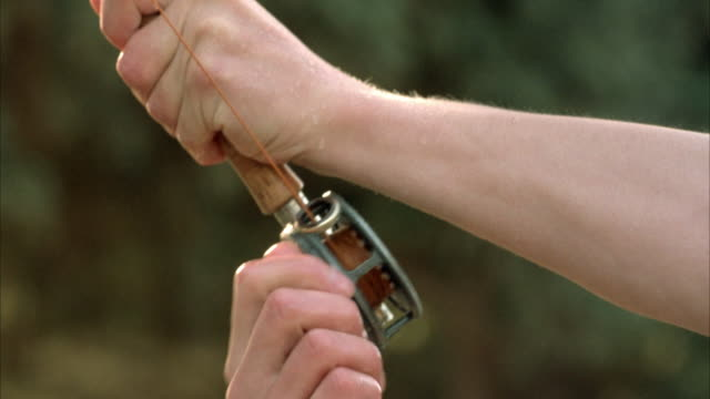 MEDIUM ANGLE OF FISHER'S HAND AND FOREARM AS HE HOLDS ONTO FISHING POLE AND REELS IN LINE.