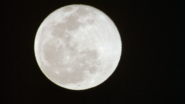 PAN DOWN SLOWLY OF FULL MOON IN CLEAR SKY.