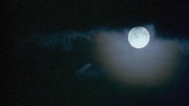PAN DOWN FROM FULL MOON TO DARKNESS.
