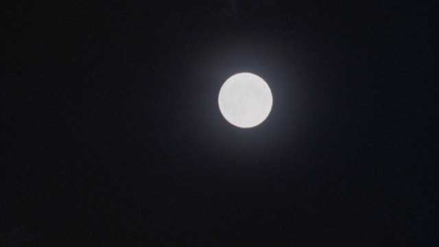 PAN DOWN AND LEFT OF FULL MOON TO DARKNESS. PANS DOWN AT FIRST, THEN QUICKLY PANS BACK UP, THEN SLOWLY DOWN.
