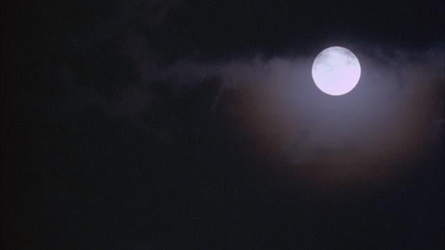 MEDIUM ANGLE OF FULL MOON IN SKY. PANS DOWN LEFT.