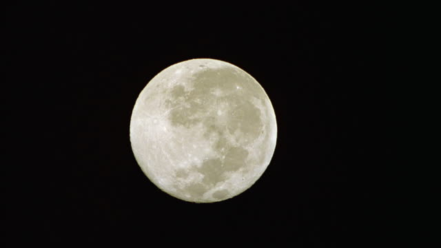 UP ANGLE OF LARGE, FULL MOON IN CENTER OF FRAME. MOON MOVES UP VERY SLOWLY.