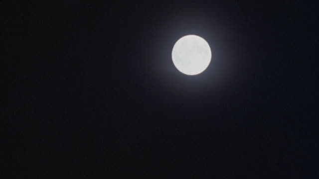 PAN DOWN AND LEFT OF FULL MOON TO DARKNESS.