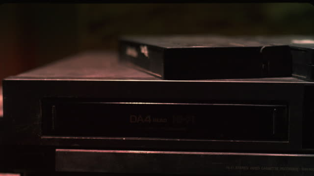 CLOSE ANGLE OF VCR WITH DUSTY VIDEO TAPES STACKED ON TOP. A HAND GRABS A TAPE EJECTED FROM THE VCR, PLACES IT ON TOP, AND INSERTS ANOTHER TAPE.