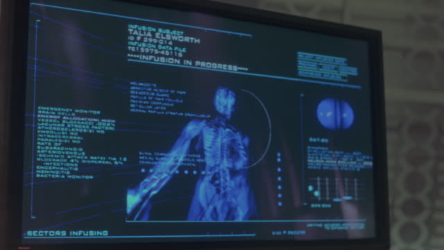 MEDIUM ANGLE OF BLACK FLAT COMPUTER SCREEN. SEE PICTURES OR ANIMATIONS OF HUMAN BODY. SEE FUTURISTIC SIGNS AND TEXT ON SCREEN. SEE BLUE TEXT AND PICTURES.