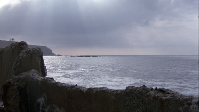 WIDE ANGLE OF OCEAN AND SHORE, COULD BE INLET. SHORE GOES FROM FOREGROUND TO LEFT.