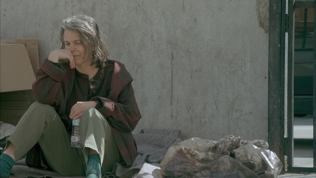 MEDIUM ANGLE OF HOMELESS WOMAN SITTING ON CARDBOARD PIECES ON SIDEWALK. WOMAN DRINKS BOTTLED WATER.